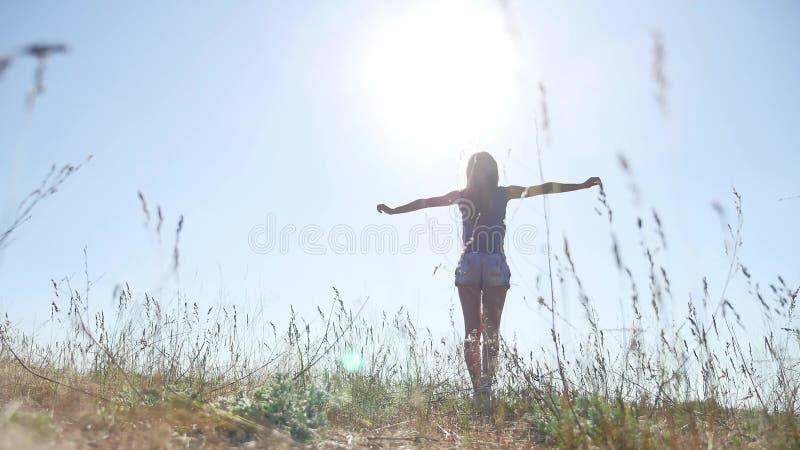 Viajes La mujer joven de la muchacha arma aumentado gozando del aire fresco en naturaleza de la luz del sol de la hierba fotos de archivo libres de regalías