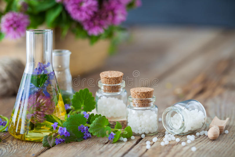 Vials of tincture of healthy herbs and bottles of homeopathy globules. royalty free stock photography
