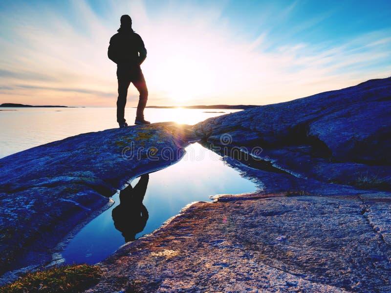 Viandante in abiti sportivi scuri con i pali e lo zaino sportivo Traccia della linea costiera sulla riva rocciosa Il turista solo fotografia stock libera da diritti