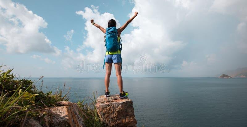 Viandante a braccia aperte sulla cima della montagna della spiaggia fotografie stock libere da diritti