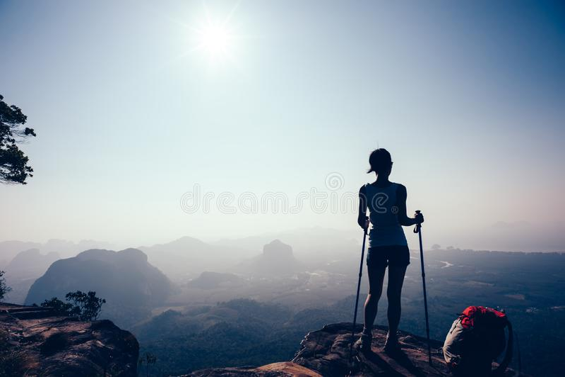 Viandante che fa un'escursione sul picco di montagna di tramonto fotografie stock