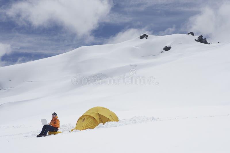Viandante che per mezzo del computer portatile dalla tenda sul pendio di montagna di Snowy fotografie stock libere da diritti