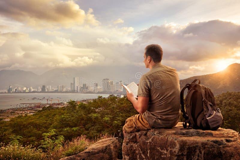 Viandante con lo zaino che si siede sopra la montagna che gode del coa di vista immagini stock libere da diritti