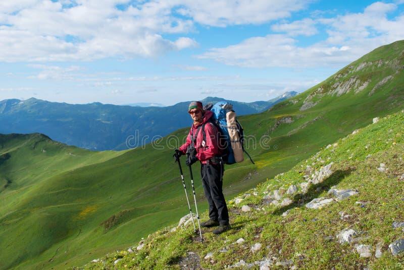 Viandante con lo zaino in montagne immagini stock