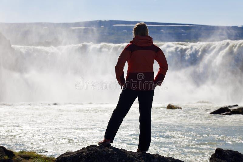 Viandante della donna che si leva in piedi davanti ad una cascata enorme fotografie stock libere da diritti