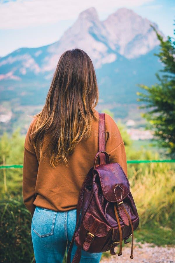 Viandante della donna con una borsa di cuoio e con il mont di Pedraforca nei precedenti fotografia stock libera da diritti