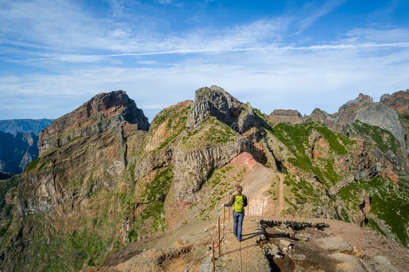 Viandante della donna sul percorso pericoloso fra le scogliere rocciose di Pico Arieiro fotografia stock