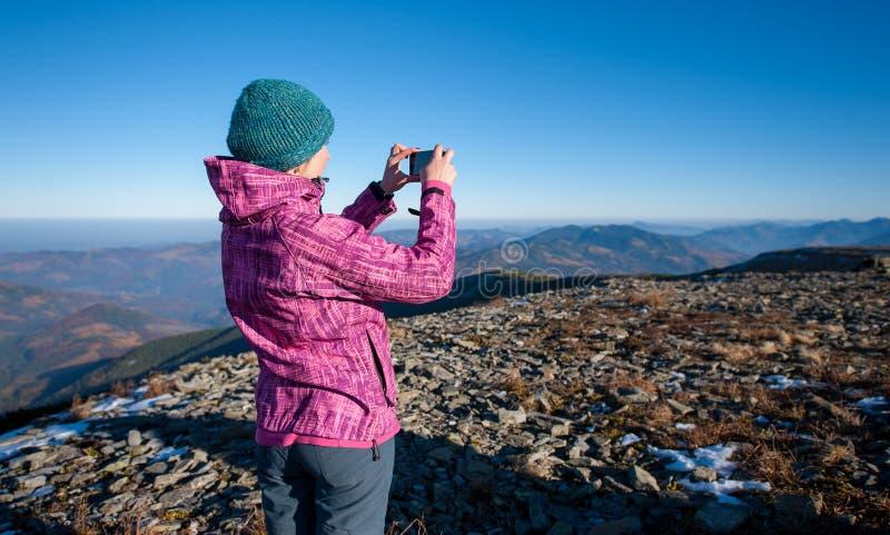 Viandante della giovane donna che prende immagine con il suo smartphone immagini stock libere da diritti
