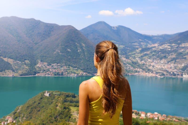 Viandante della giovane donna stando piena d'ammirazione una vista della vetta che guarda fuori sopra le catene di montagne e le  immagini stock libere da diritti