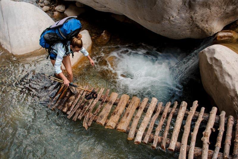 Viandante femminile che guada attraverso il fiume fra le scogliere fotografia stock libera da diritti
