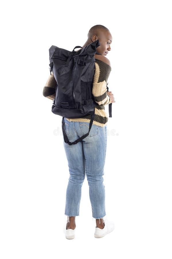 Viandante femminile nera che indossa uno zaino su un fondo bianco fotografia stock libera da diritti
