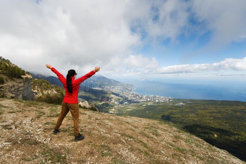 Viandante incoraggiante della donna a braccia aperte al picco di montagna, alle mani di diffusione della ragazza con gioia ed all immagine stock libera da diritti