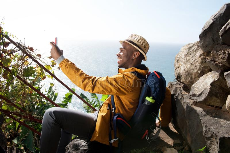 Viandante maschio afroamericana felice che si rilassa e che prende selfie fotografia stock libera da diritti