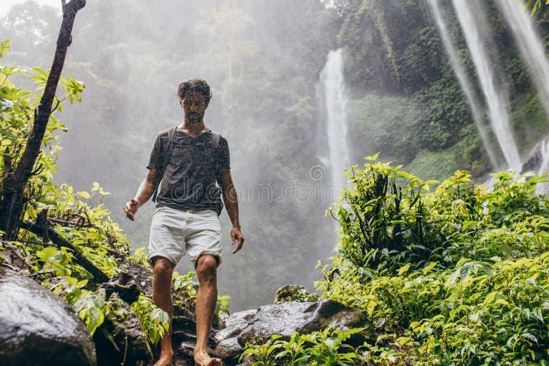 Viandante maschio che cammina giù la traccia di montagna fotografia stock libera da diritti