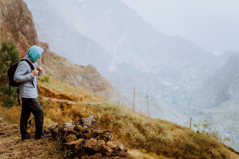 Viandante maschio che guarda giù alla valle di Xo-Xo Isola di Santo Antao, Capo Verde Il viaggiatore sull'escursione della scogli fotografia stock