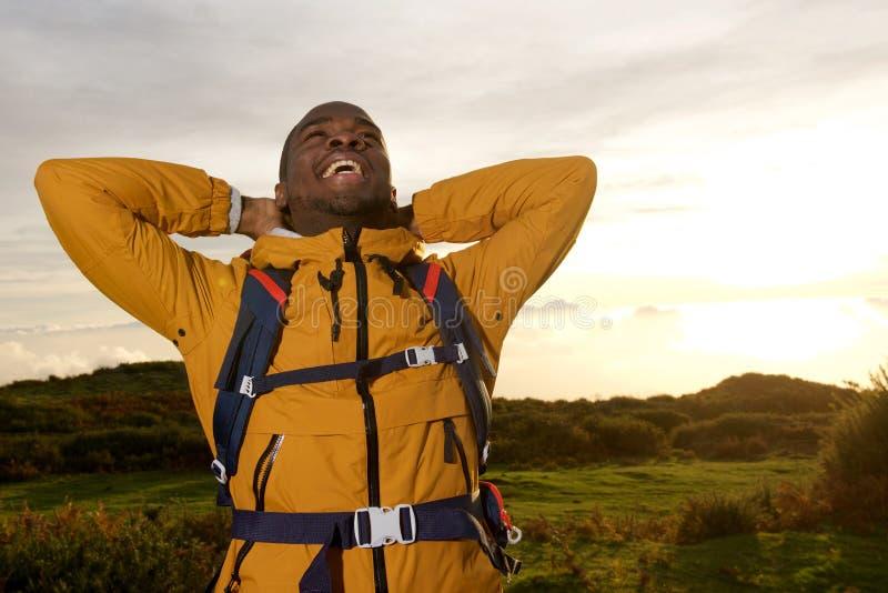 Viandante maschio felice che si rilassa con le mani dietro la testa durante il tramonto immagini stock libere da diritti