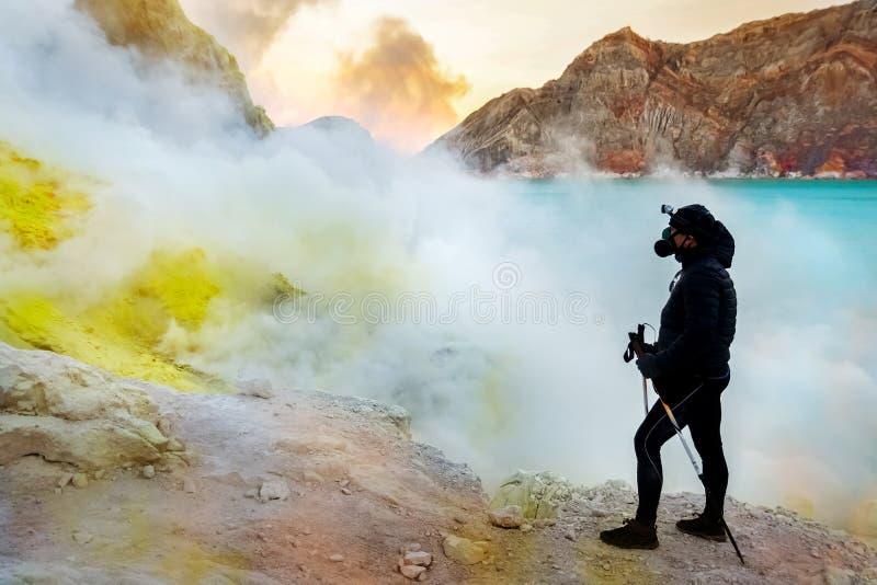 Viandante nel cratere di un vulcano Rocce dello zolfo, lago acido blu vulcanico e fumo Un viaggio pericoloso nel cratere di un at fotografia stock libera da diritti