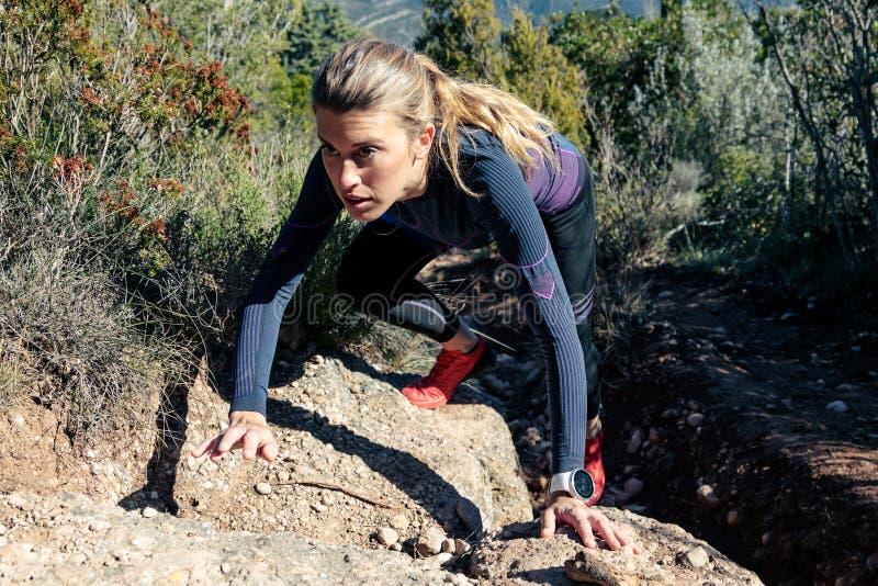 Viandante sportiva della giovane donna che scala terreno roccioso ripido sulla montagna immagine stock libera da diritti