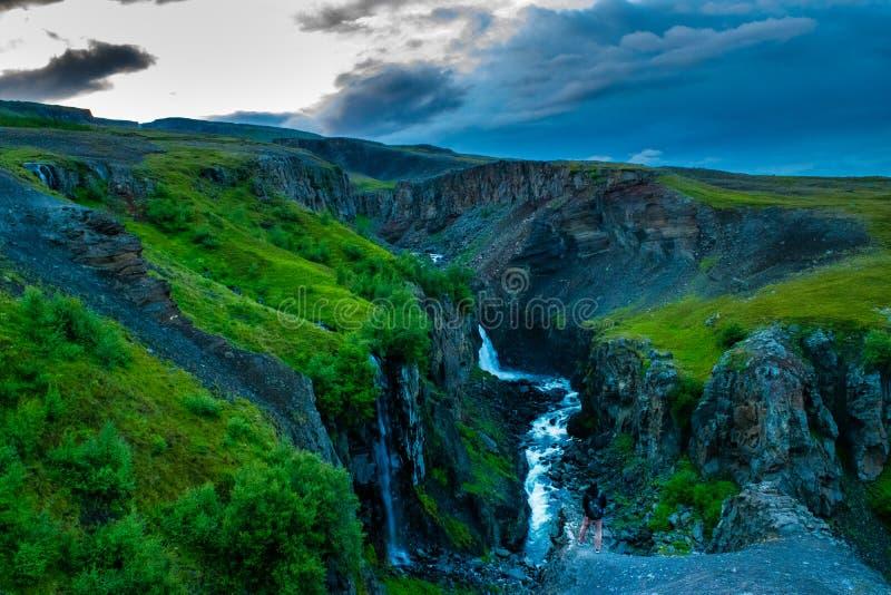Viandante su un bordo della scogliera nel parco nazionale di Skaftafell, Islanda fotografia stock