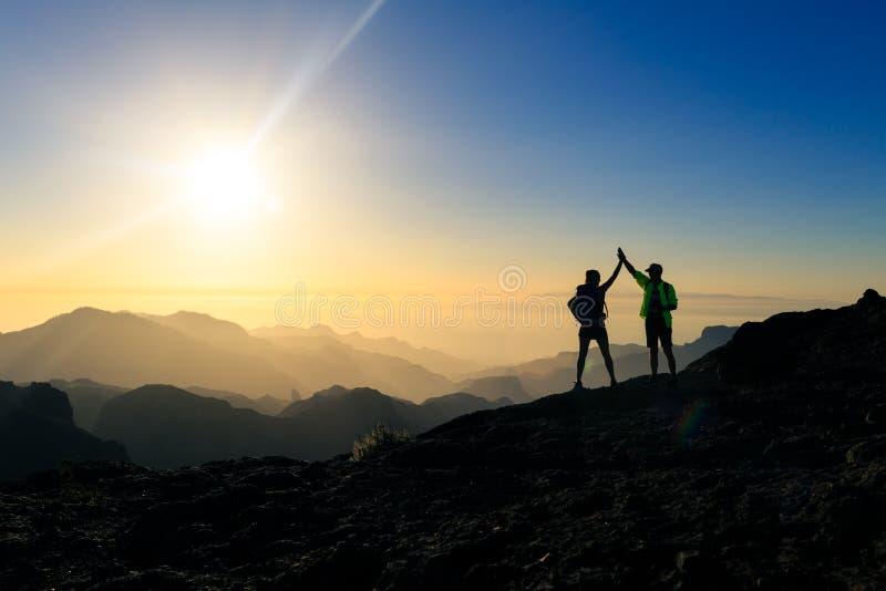 Viandanti delle coppie che celebrano concetto di successo in montagne fotografie stock