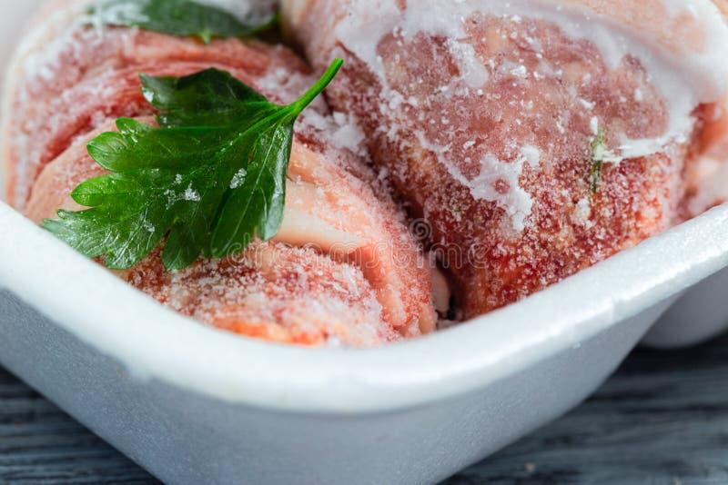 Viande congelée en hoarfrost dans un plateau en plastique avec une feuille de persil images libres de droits