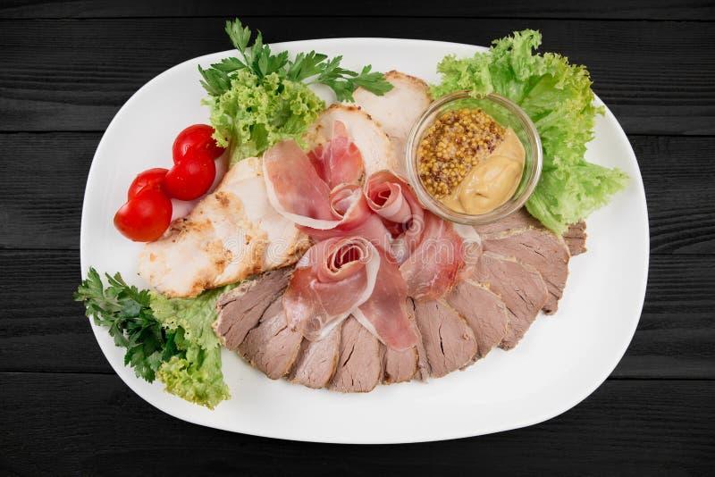 Viande coupée en tranches d'un plat blanc sur le fond en bois noir photos libres de droits