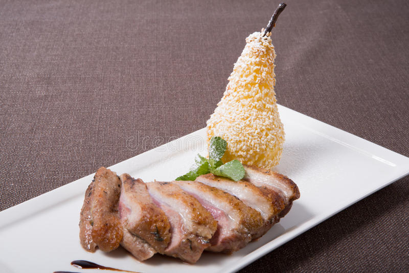 Viande coupée en tranches de canard avec la poire photo stock