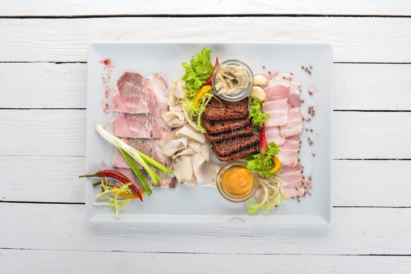 Viande coupée sur une assiette moutarde, raifort photographie stock