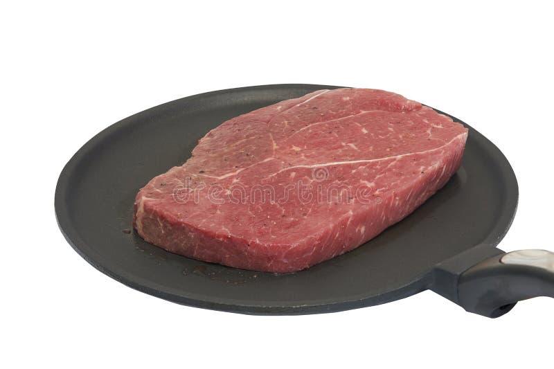 Viande crue aromatisée sur non la casserole de bâton sur le fond blanc d'isolement image libre de droits