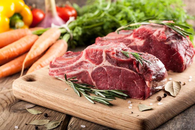 Viande crue de boeuf sur la planche à découper et les légumes frais photo stock
