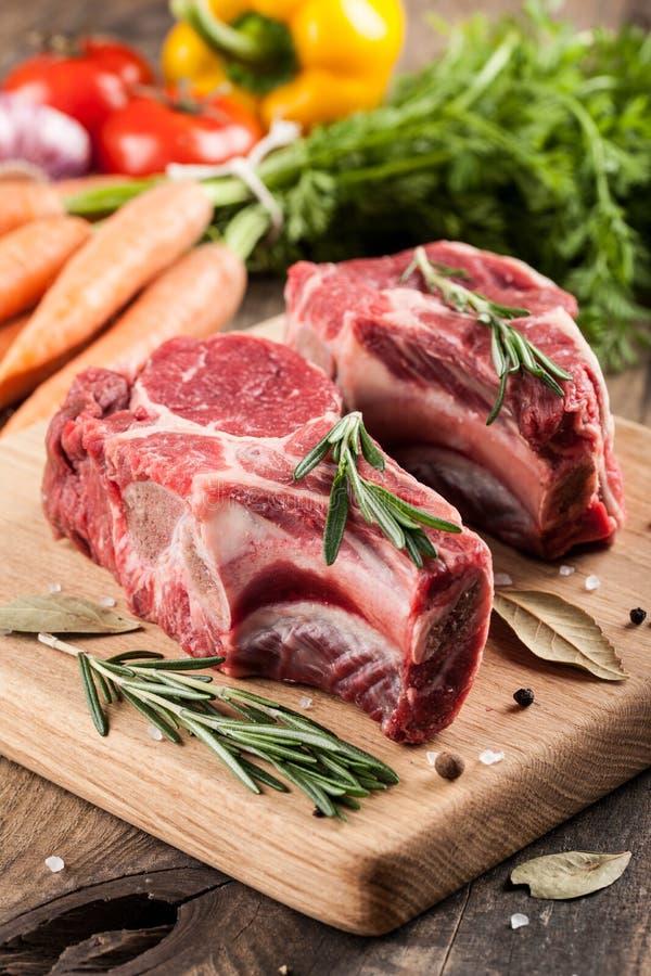 Viande crue de boeuf sur la planche à découper et les légumes frais images libres de droits