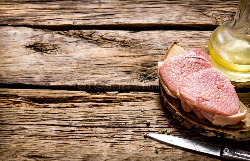 Viande crue fraîche avec le couteau et le pétrole sur un support en bois photos stock
