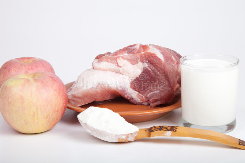 Viande crue, pommes, farine et un verre de lait La vie toujours sur la lumière photographie stock