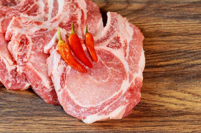 Viande crue, porc de bifteck sur une planche à découper en épices marinade, fond avec de mariner la viande image stock