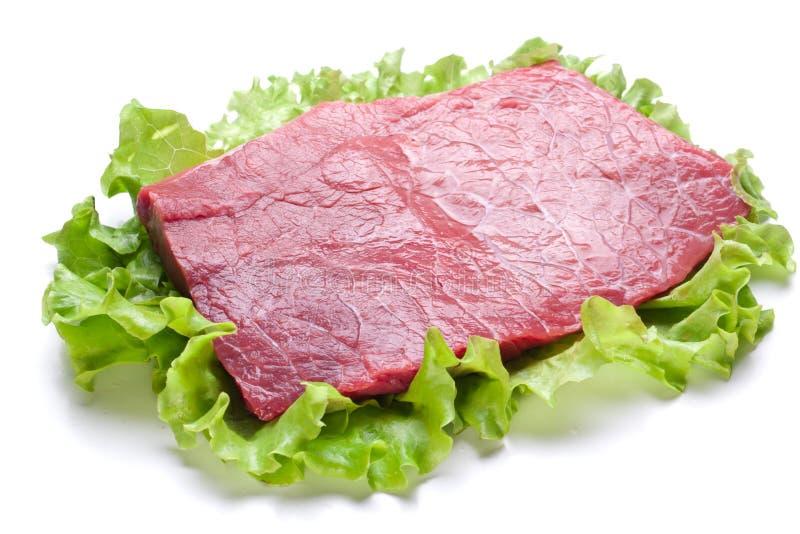 Viande crue sur des lames de laitue. images stock