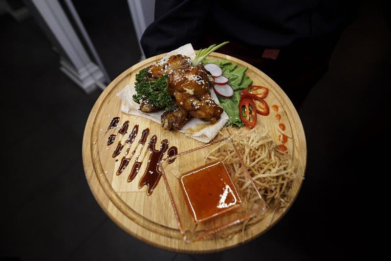 Viande cuite au four avec de la sauce et les légumes frais sur un conseil en bois image stock