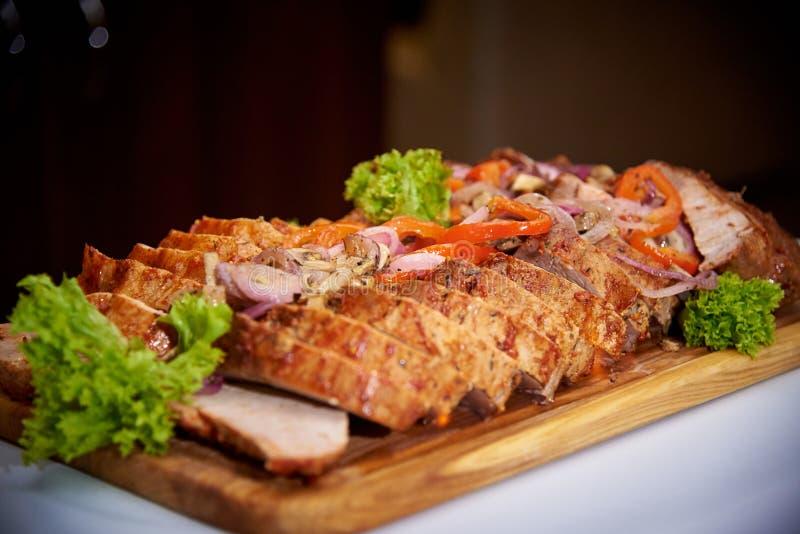 Viande cuite au four coupée en tranches avec de la sauce sur un conseil en bois image libre de droits