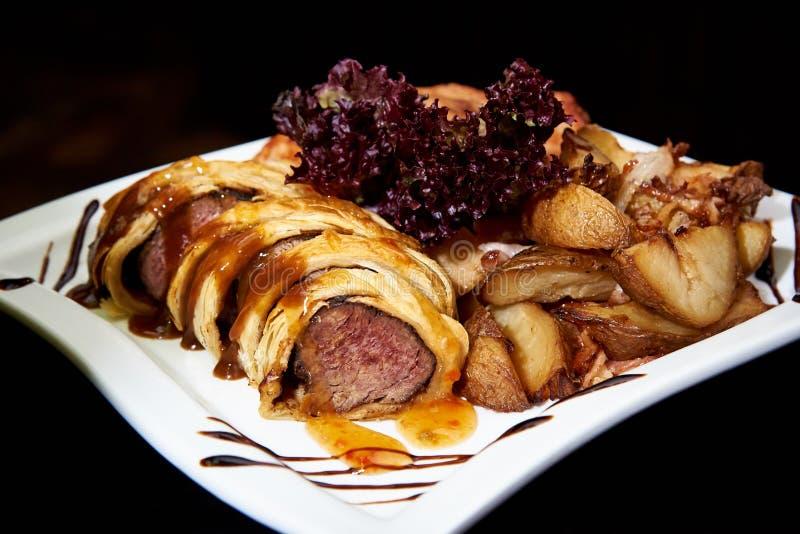 Viande cuite au four en pâte feuilletée avec les légumes et la sauce d'un plat blanc sur un fond foncé photographie stock libre de droits
