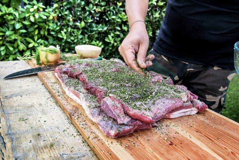 Viande de assaisonnement de boucher avec du sel et des herbes pour roulé vers le haut du porc photo libre de droits