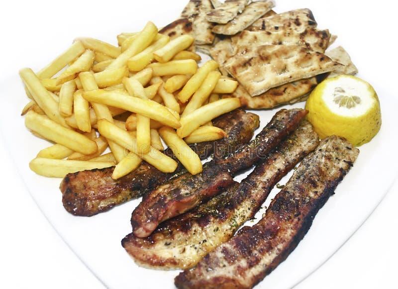 viande de bifteck avec les pommes de terre frites et le pain pita grec photo stock