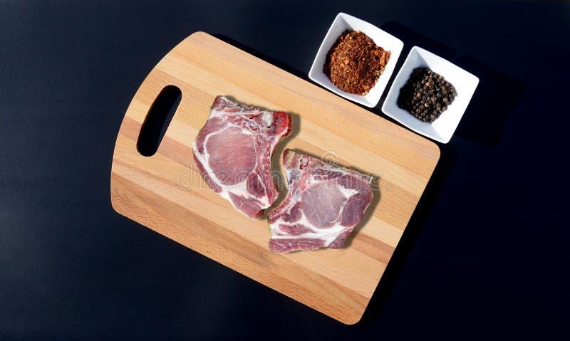 Viande de porc crue sur une planche à découper et un poivre photos stock