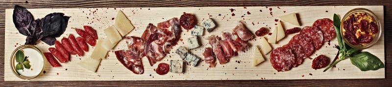 Viande et fromage sur un conseil en bois décoré des sauces à basilic photo stock