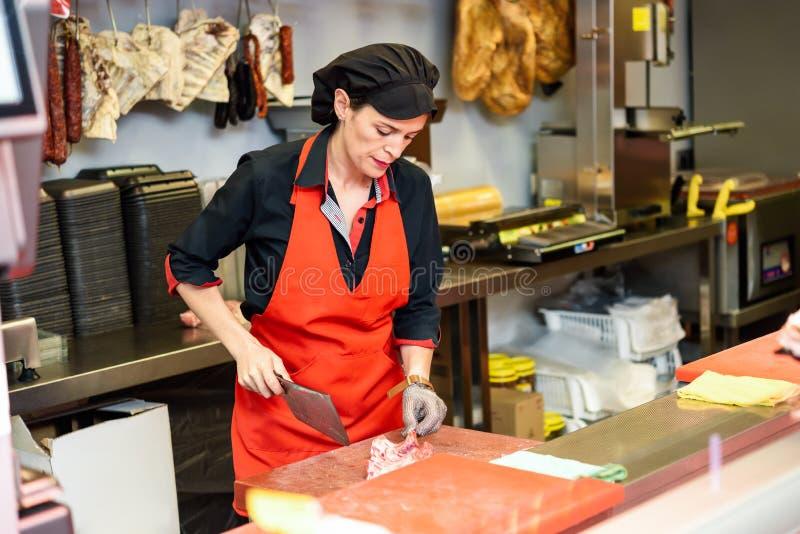 Viande femelle de coupe de boucher au compteur dans la boucherie photo stock