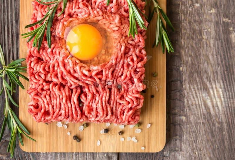 Viande fraîche de boeuf haché avec l'oeuf et les assaisonnements photographie stock
