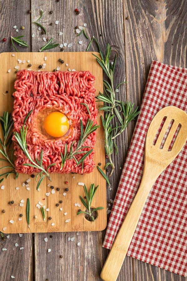 Viande fraîche de boeuf haché avec l'oeuf et les assaisonnements photos stock