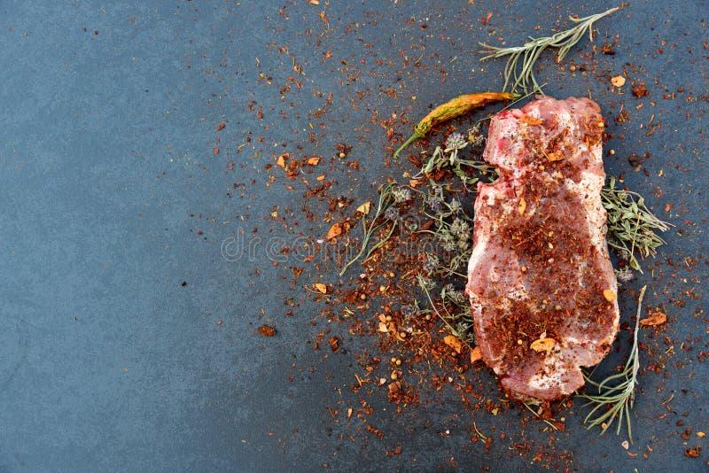 Viande fraîche et herbes aromatiques sur l'obscurité photo stock
