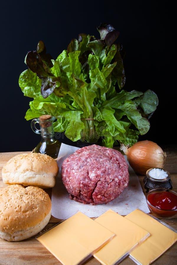 Viande, fromage, oignons, herbes, sel, ketchup sur un ove en bois de table photos stock