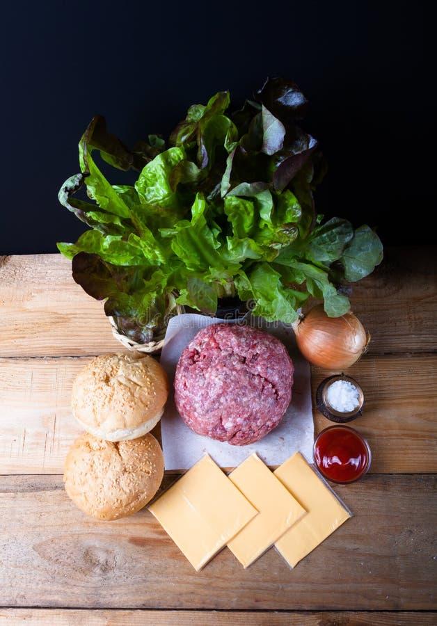 Viande, fromage, oignons, herbes, sel, ketchup sur un ove en bois de table photographie stock libre de droits