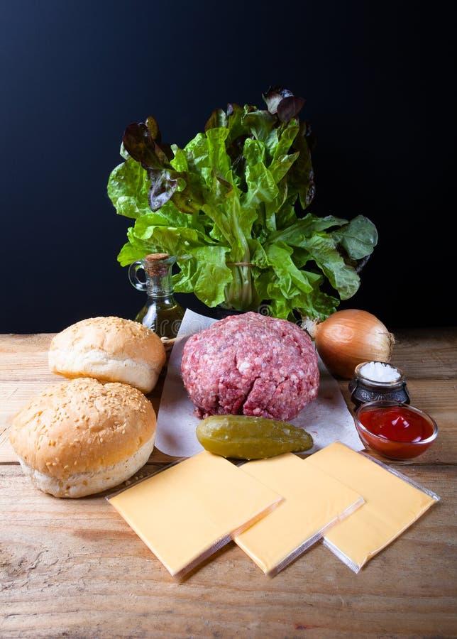 Viande, fromage, oignons, herbes, sel, ketchup sur un ove en bois de table photos libres de droits