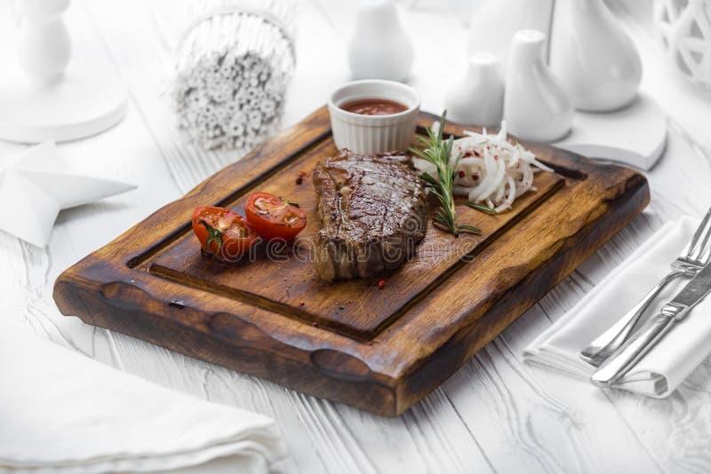Viande grillée aux oignons et à la sauce d'accompagnement sur un conseil photos stock